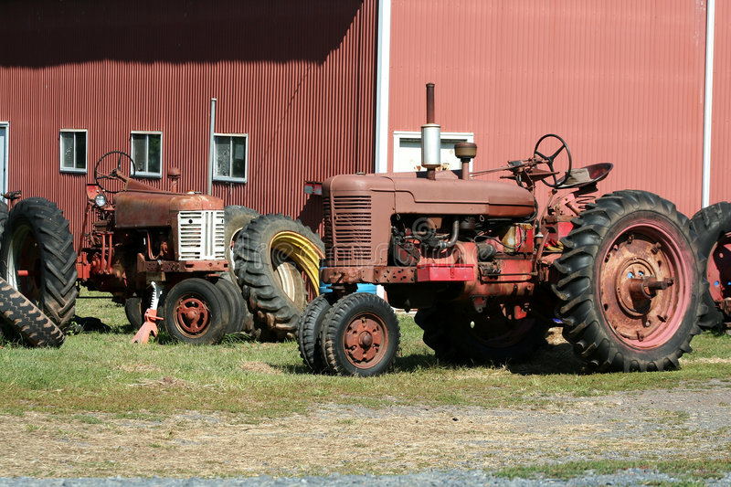 Old red tractors. Two Old red tractors with tires royalty free stock images