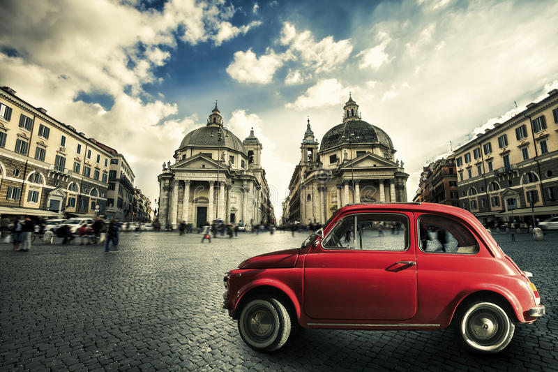 Old red vintage car italian scene in the historic center of Rome. Italy. Piazza del Popolo in Rome. An old small red car is parked in the historic center of stock photo