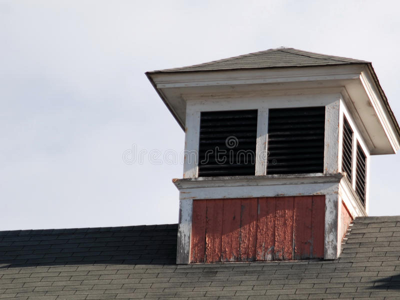 Old red and white cupola sitting on a roof on a bright fall day royalty free stock image