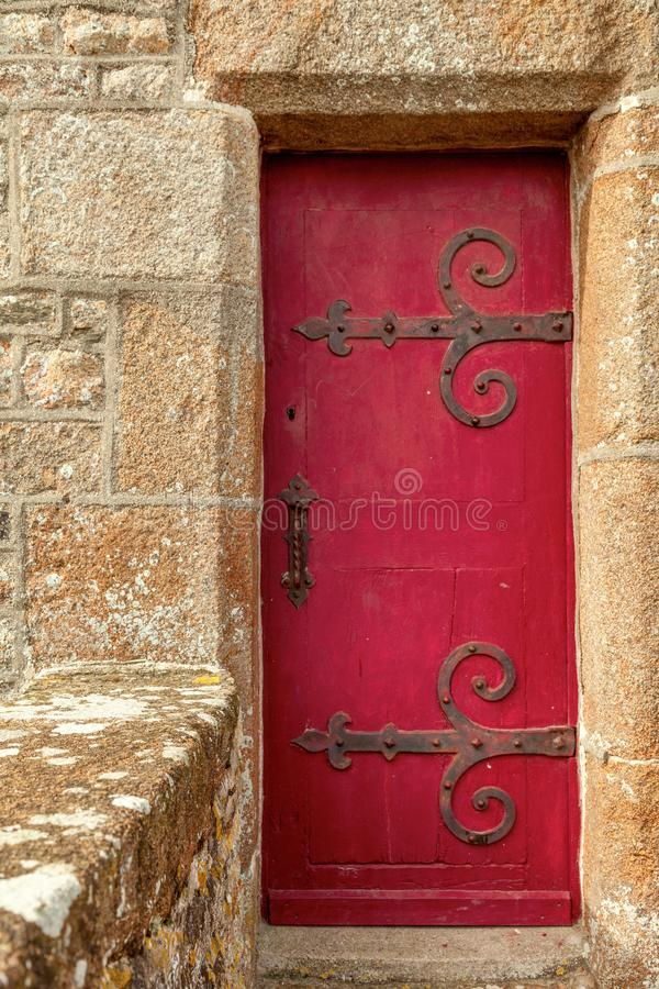 Red wooden door. Old red wooden door in a stone frame royalty free stock photo
