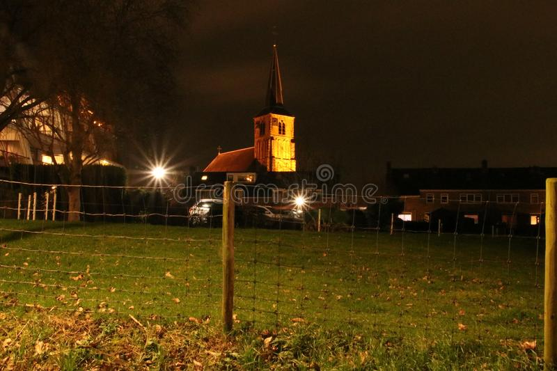 The old reformed church in Nieuwerkerk aan den IJssel iluminated by orange light royalty free stock photo
