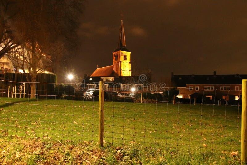 The old reformed church in Nieuwerkerk aan den IJssel iluminated by orange light in the night. royalty free stock image