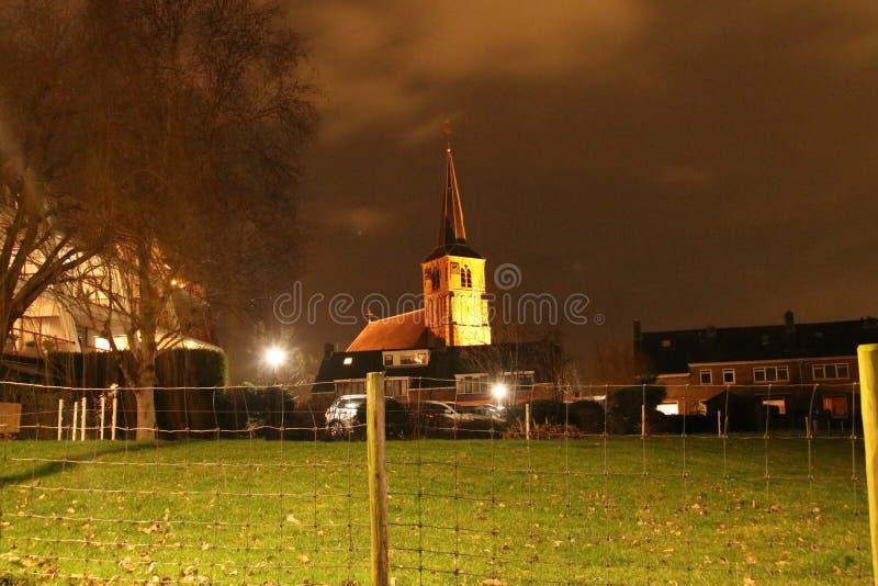 The old reformed church in Nieuwerkerk aan den IJssel iluminated by orange light in the night. royalty free stock photos