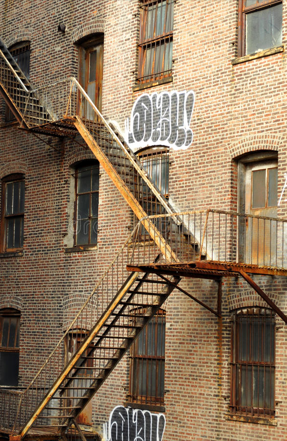 Old residential building with exterior rusty fire. Escape stairways and graffiti paintings on the walls in New York city, United States of America stock image