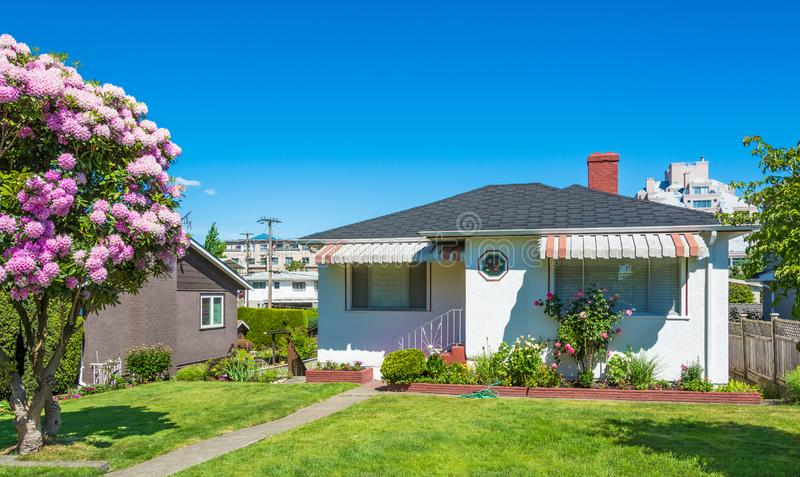 Old residential house in Vancouver with stripy aprons above the windows. And green lawn of front yard stock image