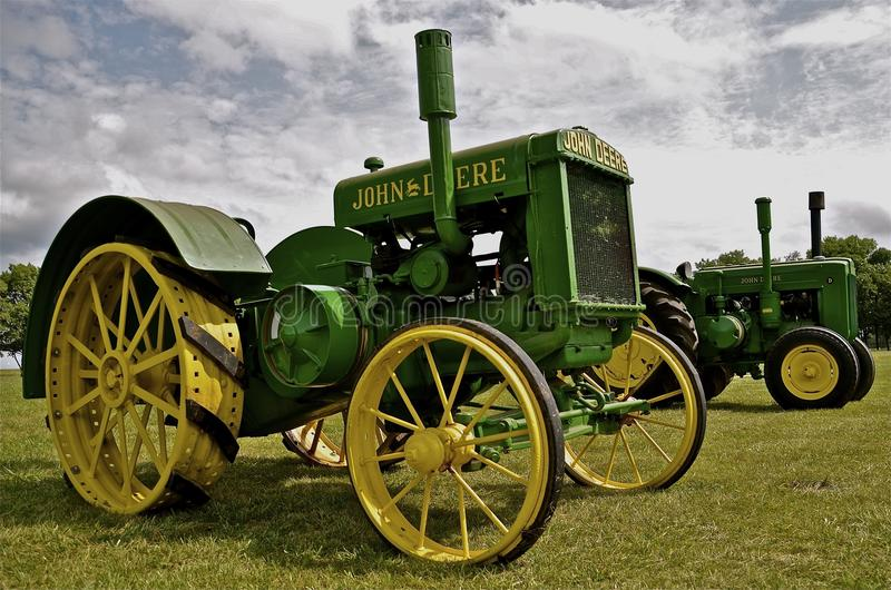 Old restored John Deere tractors on display. MADISON, SD, AUGUST 15 2014: Old restored John Deere D tractors are on display at the Prairie Viilage where 1000's stock image