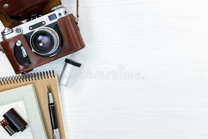 Old retro camera in leather cover, notebook, pen, and roll film royalty free stock image