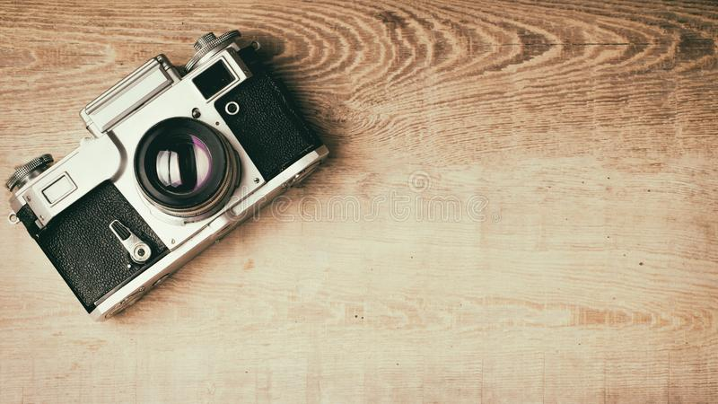 Old retro camera on vintage rustic wooden planks boards. Education photography courses back to school concept abstract background royalty free stock image