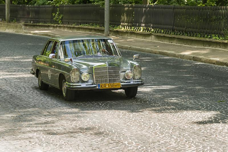 Old retro car  Mercedes- Benz 220 SE 1963. Lviv, Ukraine - June 2, 2019: Old retro car Mercedes- Benz 220 SE 1963  with its owner and  unknown passenger taking stock photography