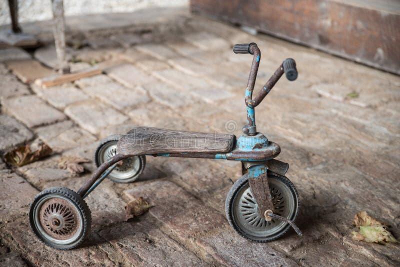 Old retro children three-wheeler on a brick floor royalty free stock photos