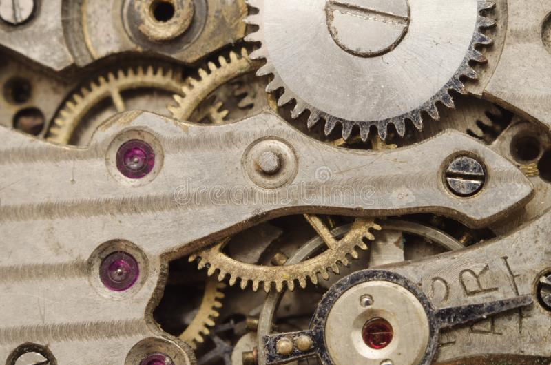 Old retro clockwork background. Clock watch mechanism with gray and golden gears royalty free stock photography