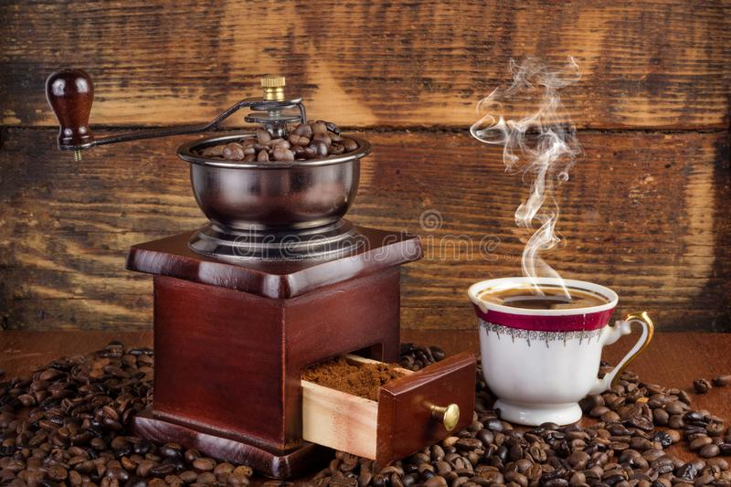 Retro coffee mill and cup with black coffee smoking on wooden background royalty free stock photography