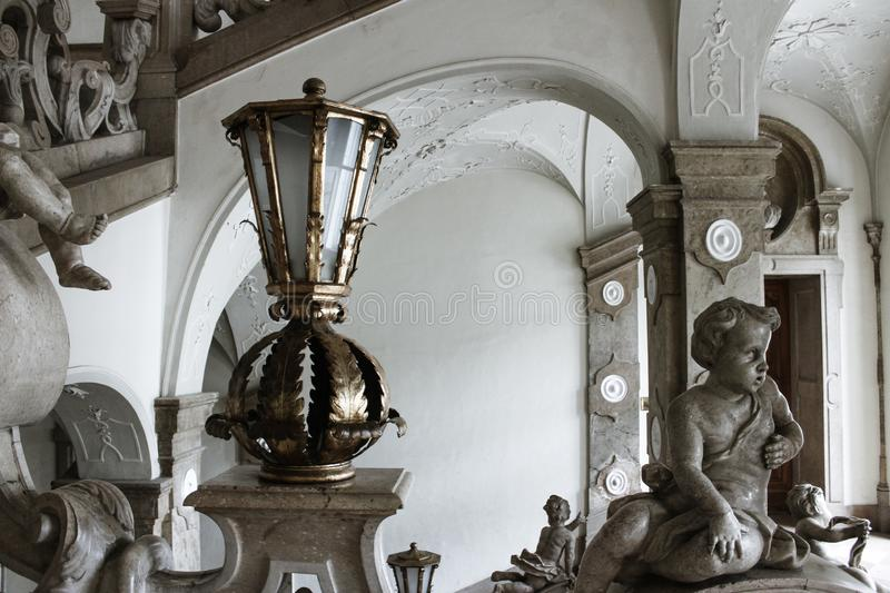 Old retro ghol gas lantern in historic palace staircase - Aged ancient lamp. Old historic lantern, in white palace - Salzburg. Ancient lantern on old staircase stock photos