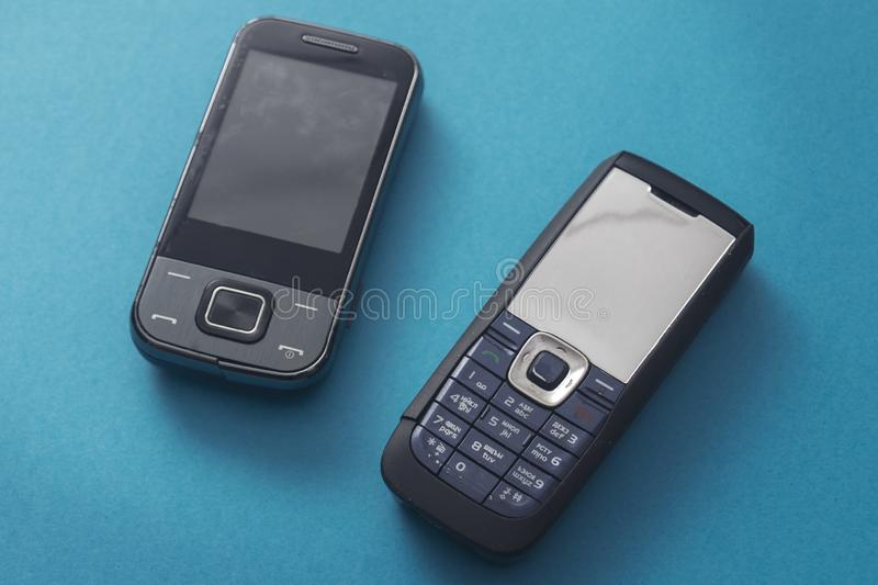 Old retro mobile phones on blue background. Close up stock images