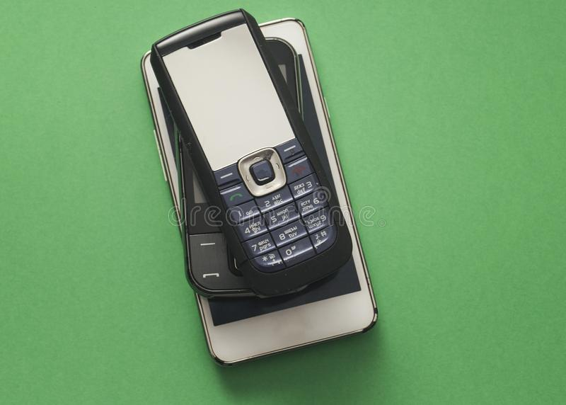 Old retro mobile phones on green background. From above royalty free stock photo
