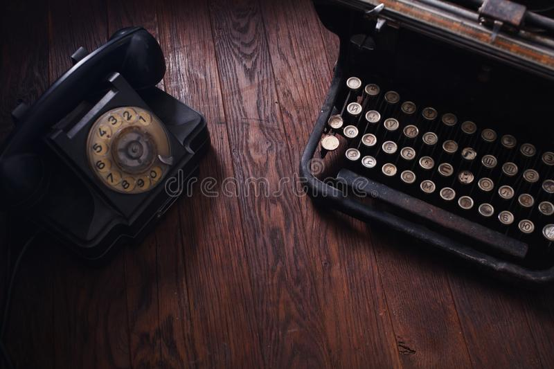 Old retro phone with vintage typewriter on wooden board. Old retro phone with vintage typewriter on wooden table royalty free stock images