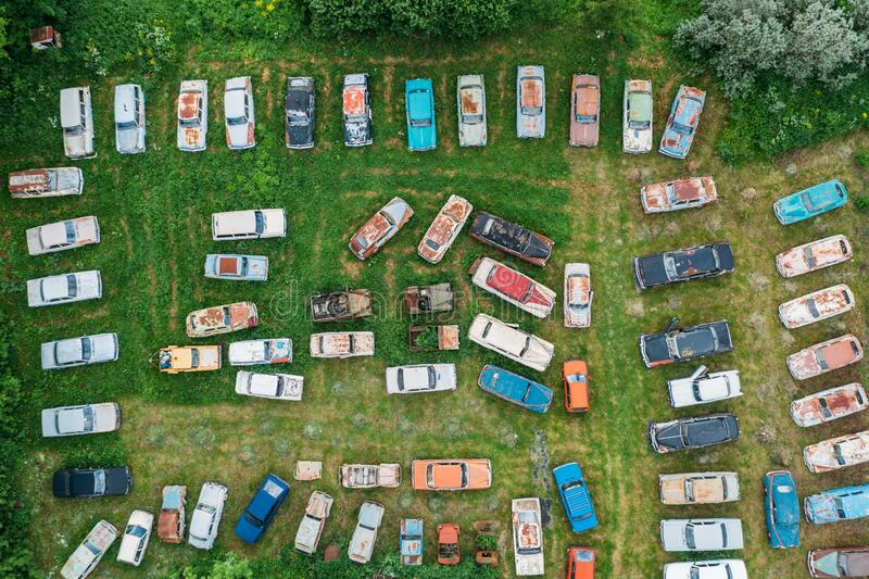 Old retro rusty abandoned cars in green grass, aerial top view from drone above cemetery of vintage autos stock photo