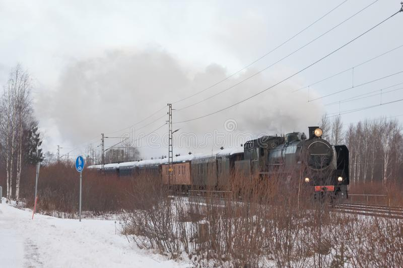Old retro steam train at winter morning in Finland royalty free stock images