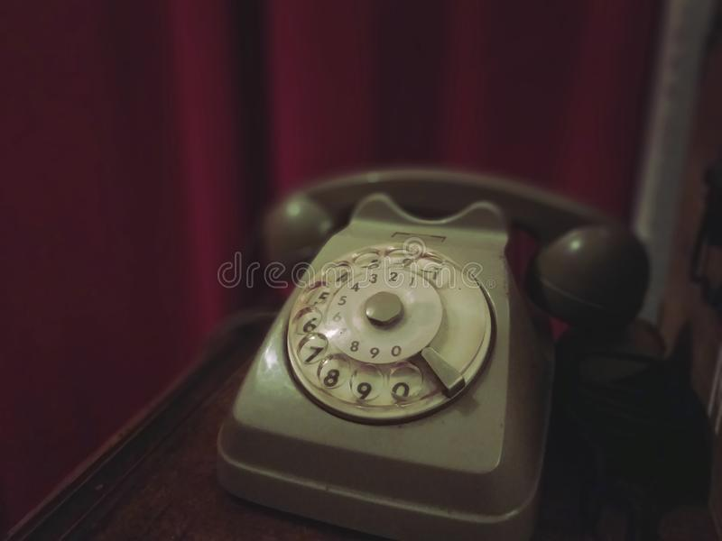 Old retro telephone on a wooden table with red curtain on the background - old photo, vintage style effect stock images