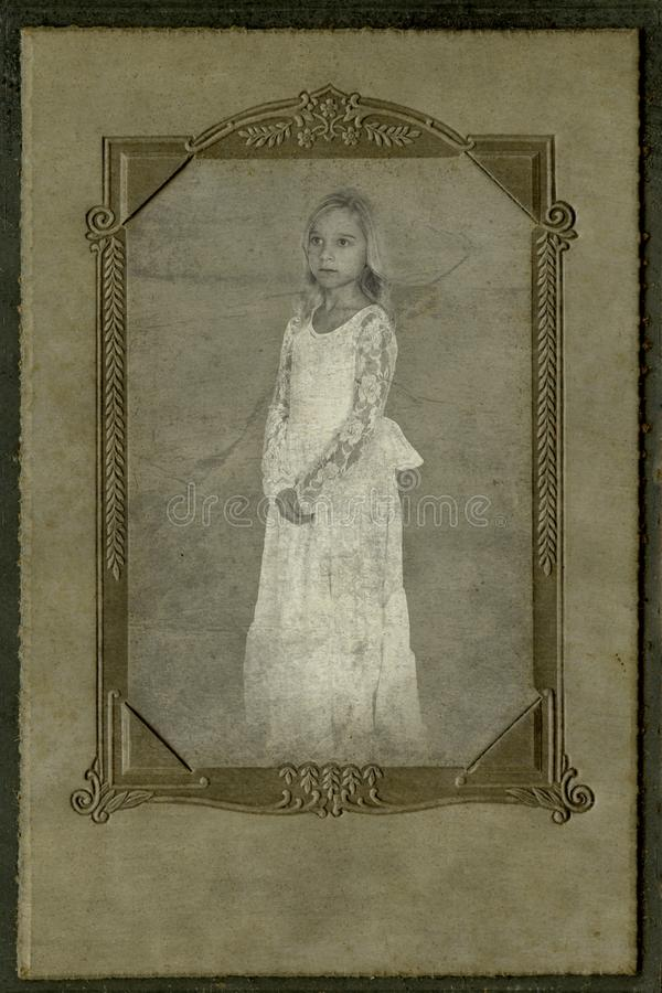 Vintage Child Portrait, Antique Photography. Old retro vintage portrait photography. A young girl in a white dress poses for a picture photograph from olden days stock photo