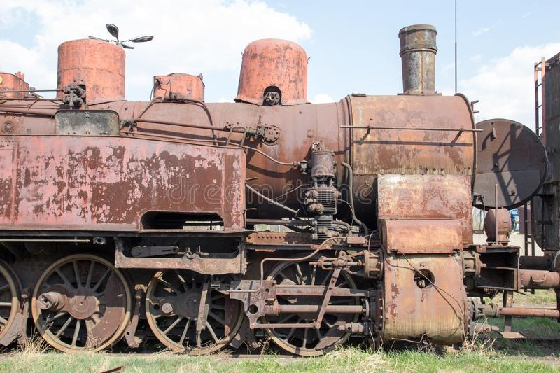 Old retro vintage rusty locomotive standing on rails, on the background of blue sky stock image