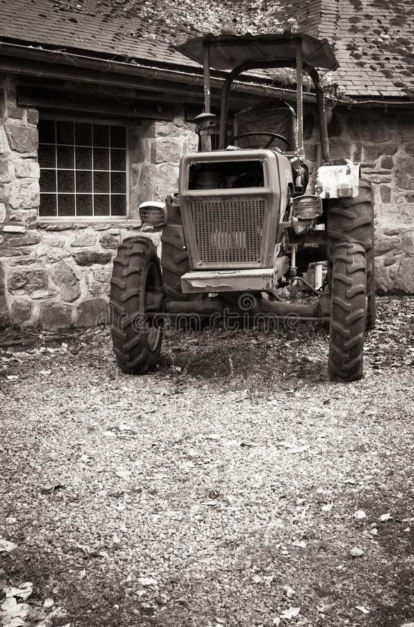 Old retro vintage tractor in countryside in balck and white sepia stock images