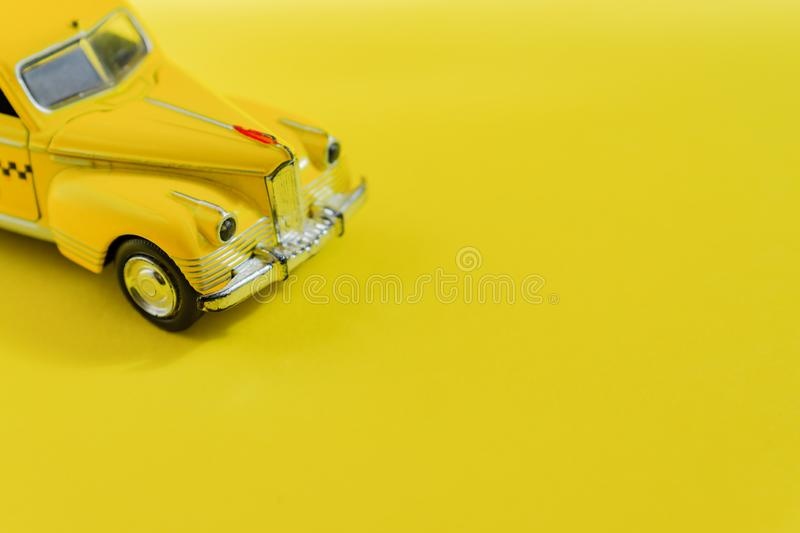 Old retro yellow toy car taxi on yellow background with copy space. Selective focus, Travel concept.  royalty free stock photography