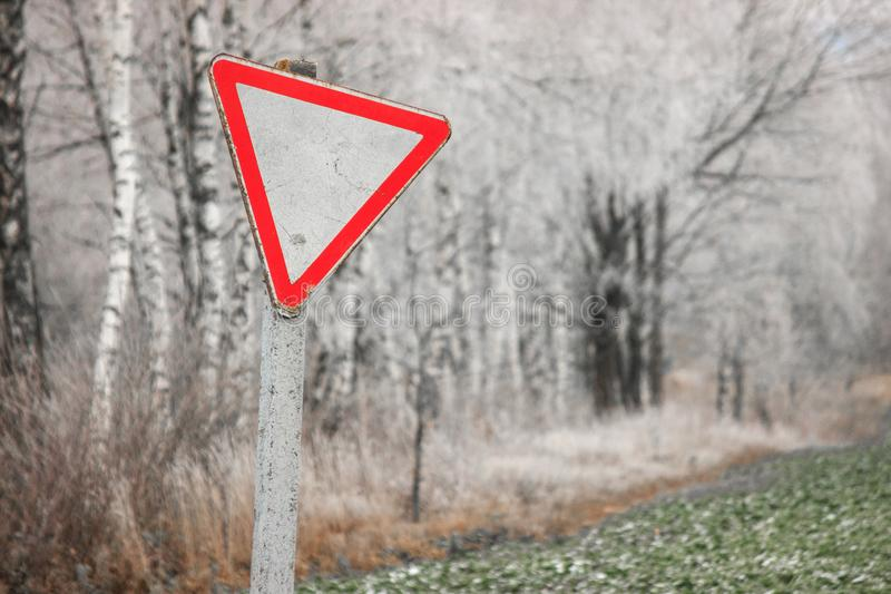 Old, rickety sign give way against the snow-covered forest and field. Road signs, rules of the road. White triangle with a red rim. Old, rickety sign give way royalty free stock images