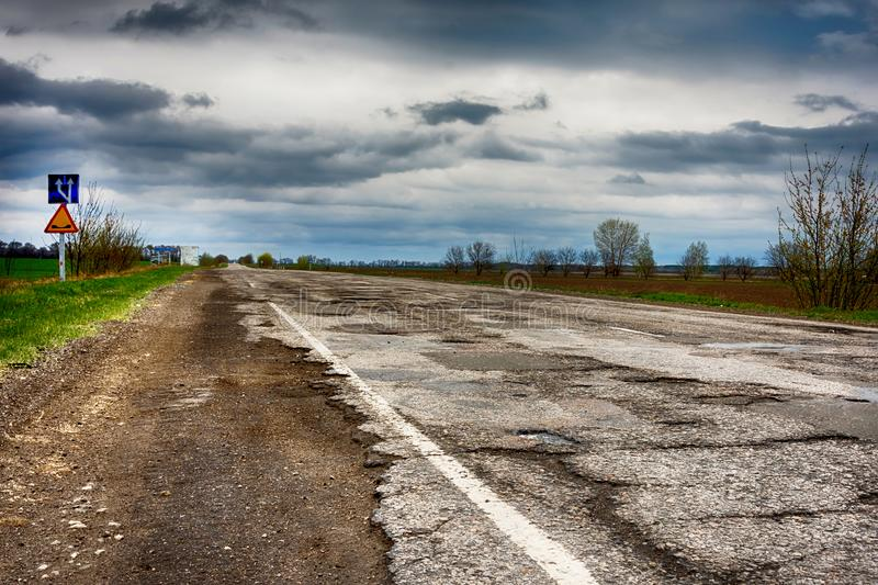 Old road. Concept highway in huge pits and potholes cloudy wea royalty free stock photo