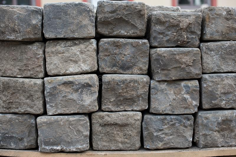 Old road granite blocks, cubes stacked together. Old stone cobbles. Old road material royalty free stock image