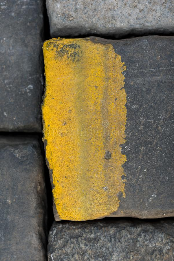 Old road tiles with yellow paint. Street, road details. Vertical background. Road cobbles stock image