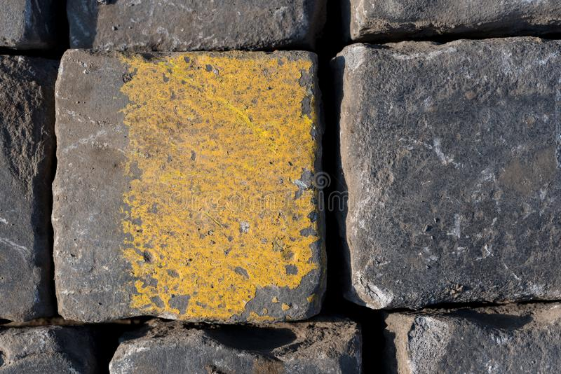 Old road tiles with yellow paint. Street, road details. Vertical background. Road cobbles royalty free stock images