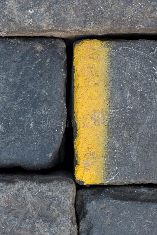 Old road tiles with yellow paint. Street, road details. Vertical background. Road cobbles stock photos