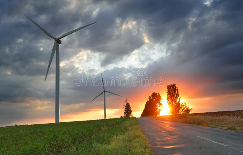 Old road and wind power generators at the sunset stock images