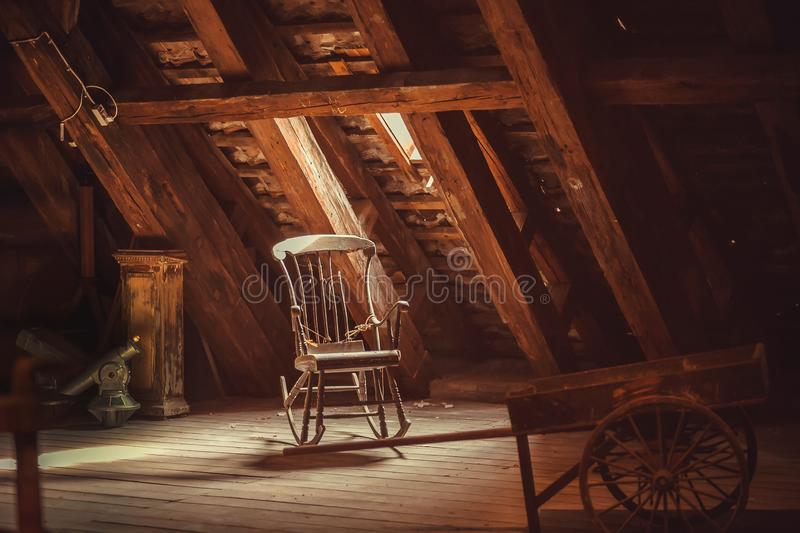 Old rocking chair in rustic vintage style attic. Memories concept stock photography