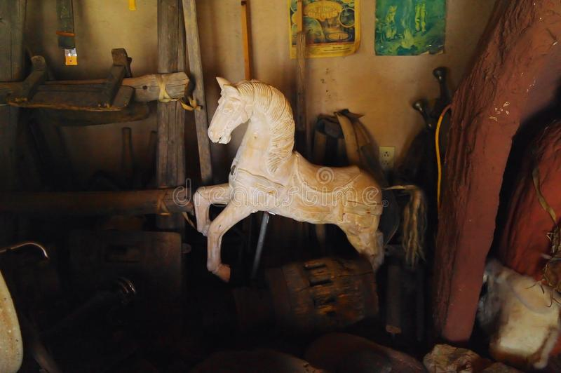 Old rocking horse left in the clutter. An old rocking horse left in the clutter in an old antique shop that seems to be frequented rarely royalty free stock photography