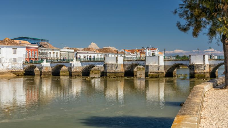Old Roman Bridge, Tavira, Portugal. The Old Roman Bridge or Ponte Antiga at low tide spanning the Gilao River in the picturesque town of Tavira in Portugal stock images