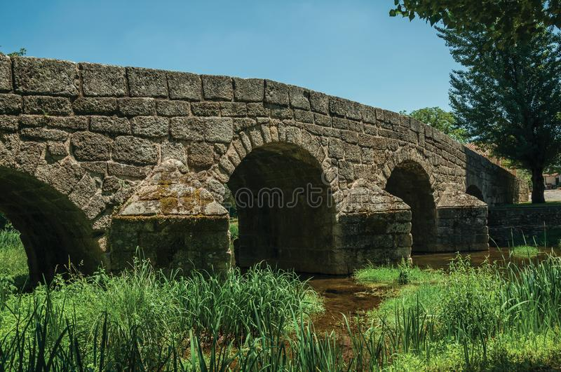 Old Roman stone bridge over the Sever River in Portagem. Old Roman stone bridge still in use over the Sever River with green plants on the bank, in a sunny day stock photos