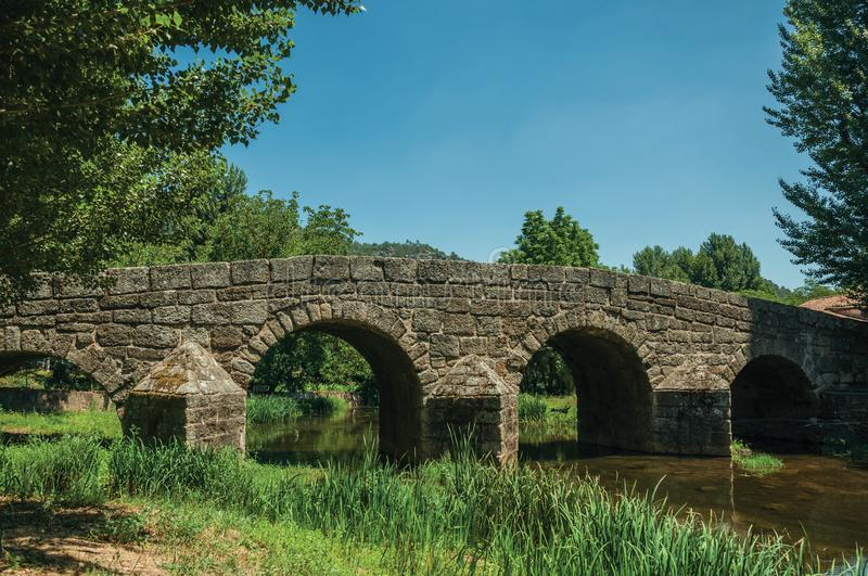 Old Roman stone bridge over the Sever River in Portagem. Old Roman stone bridge still in use over the Sever River with green plants on the bank, in a sunny day royalty free stock photos