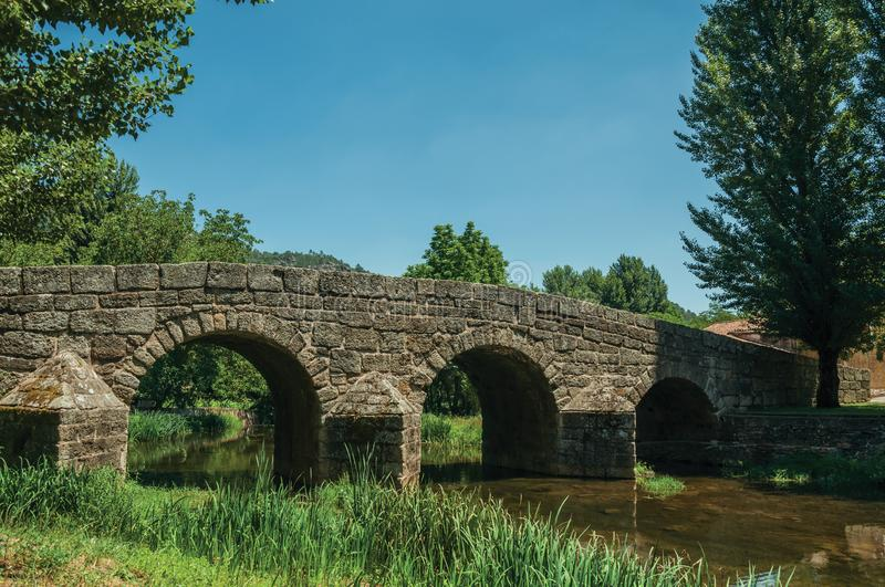 Old Roman stone bridge over the Sever River in Portagem. Old Roman stone bridge still in use over the Sever River with green plants on the bank, in a sunny day stock photo