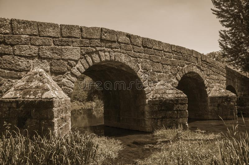 Old Roman stone bridge over the Sever River in Portagem. Old Roman stone bridge still in use over the Sever River with plants on the bank at Portagem. A district stock photo