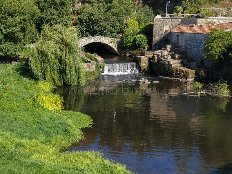 Old Roman stone bridge and waterfall on Este River in Vila do Conde, Portugal. On a sunny summer day stock image