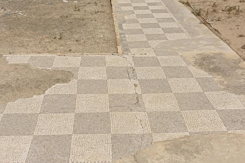 Old roman tiled walkway in chessboard pattern, detail of  Ruins of Italica,  Roman city in the province of Hispania Baetica stock photo