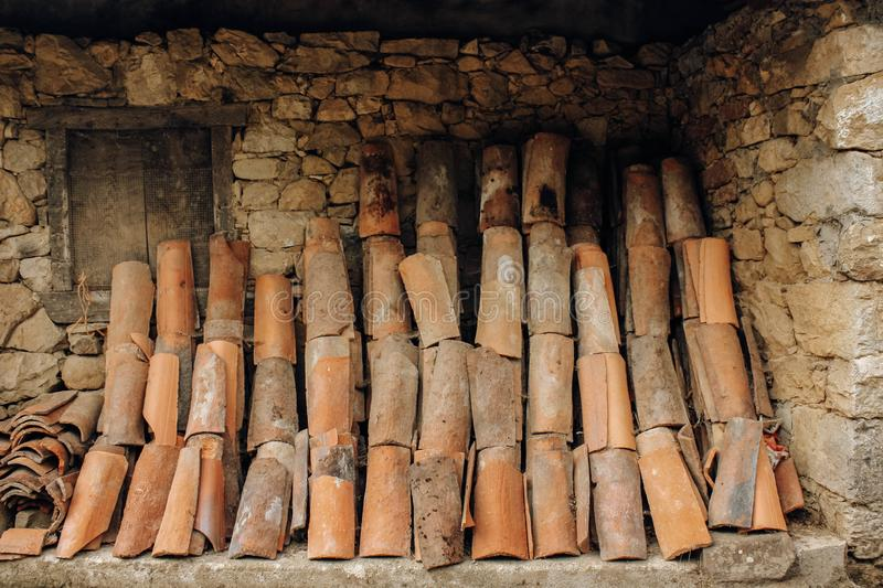 Old roof tiles placed on a stone wall of a rural house stock images