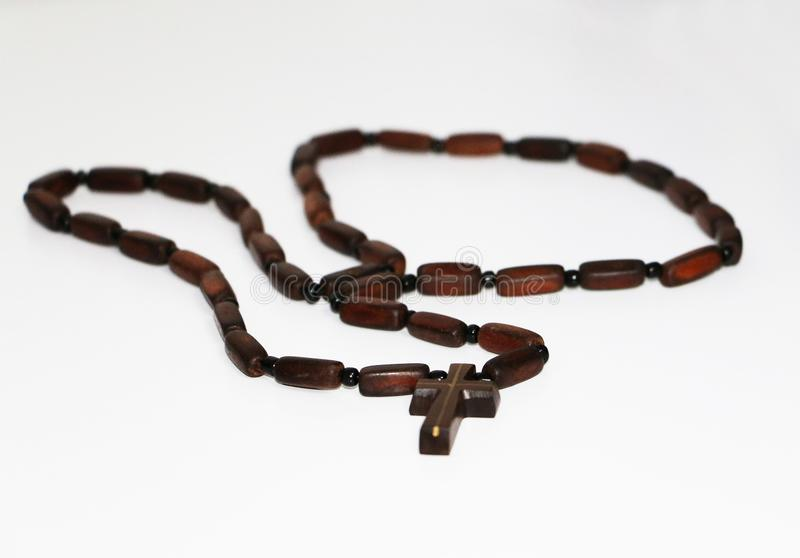 Old rosary with wooden beads laid, christian cross pendant and chain on blurred white background with blank area stock image