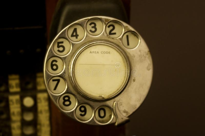 An old rotary dial telephone sits in front of a telephone exchange. A 1970s-1980s rotary dial telephone sits in front of a telephone exchange board with copy royalty free stock image
