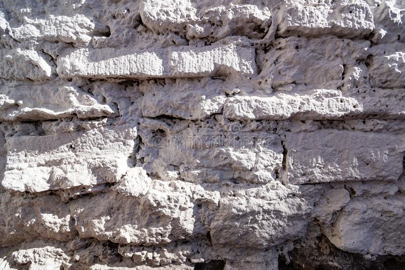 Old rough limestone wall. Texture of the old rough limestone wall stock photography