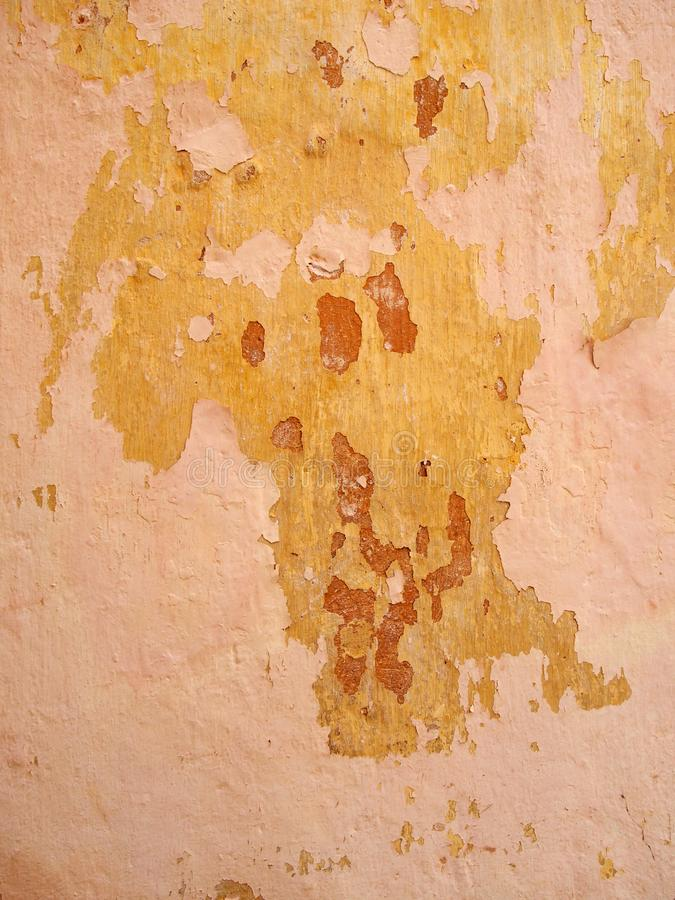 Old rough painted wall with peeling layers of pink red and yellow paint. An old rough painted wall with peeling layers of pink red and yellow paint royalty free stock image