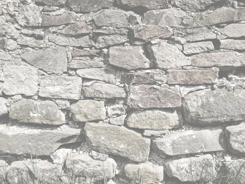 Old rough stone black and white surface wall. Exterior light background royalty free stock photos