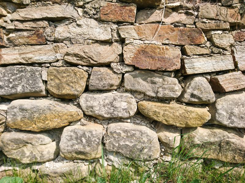 Old rough stone surface wall exterior material background. Good sun light outdoor close up royalty free stock photo
